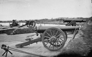 Two Model 1829 32-pounder siege and garrison guns, rifled by the James method (64-pdr James rifles). The one in the foreground is on a siege carriage. The one behind is on an iron, front pintle, barbette carriage.
