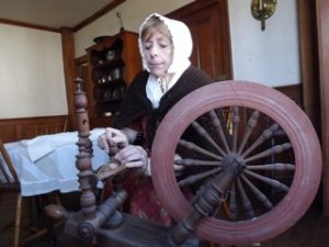 Barbara Weaver with a flax spinning wheel at the Varnum House.