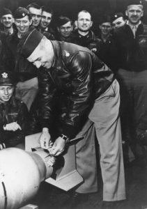 "Lieutenant Colonel Doolittle wires a Japanese medal to a bomb, for ""return"" to its originators."